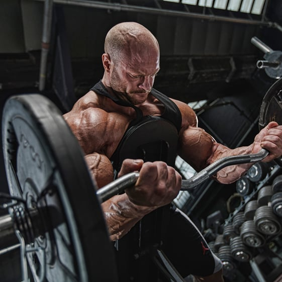James Hollingshead doing heavy biceps curls in the gym