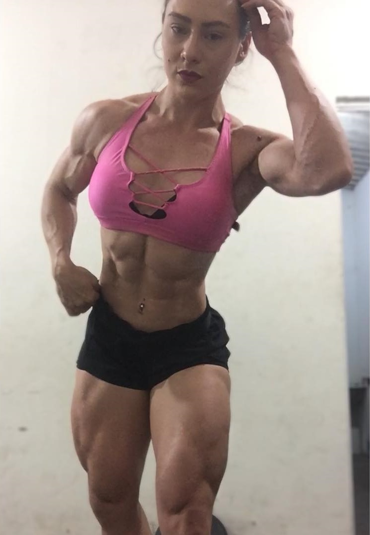 Kelly Karina flexing for the photo looking ripped and toned