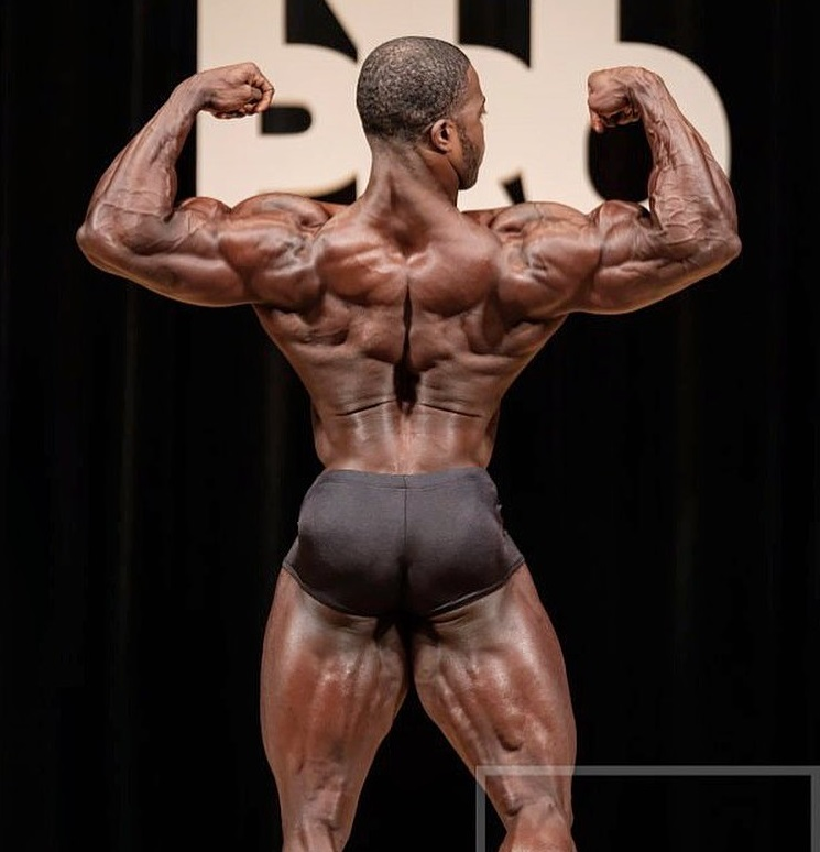 Kenneth Owens performing a back double biceps pose looking big and ripped