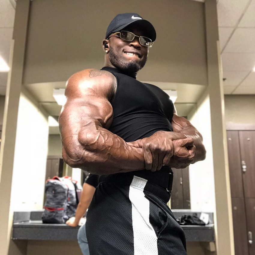 Kenneth Owens doing a side chest pose in a gym locker room