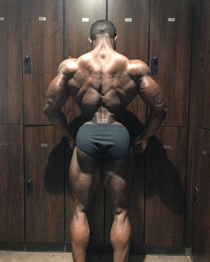 Kenneth Owens posing his ripped lats in downlighting