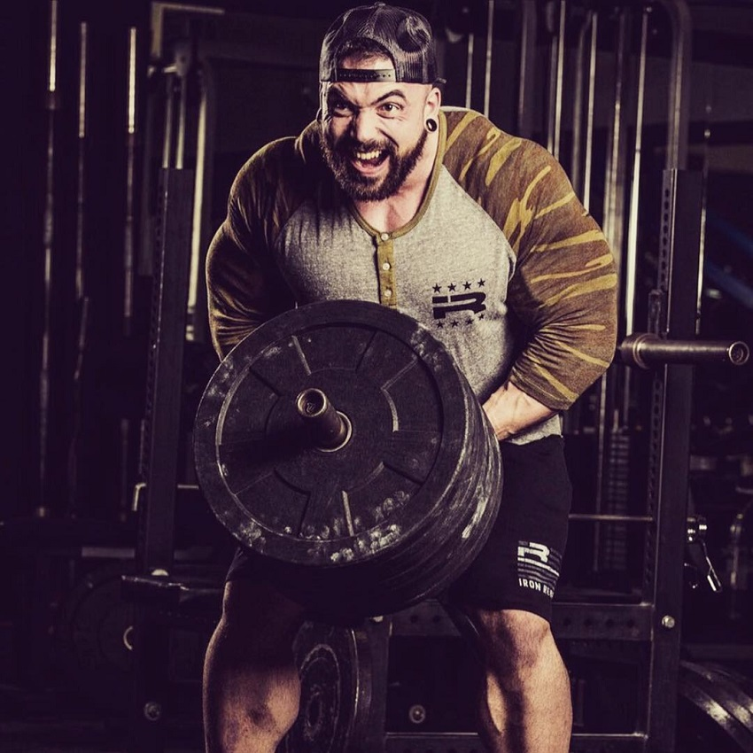 Luke Sandoe doing heavy T-bar rows with a pained expression on his face