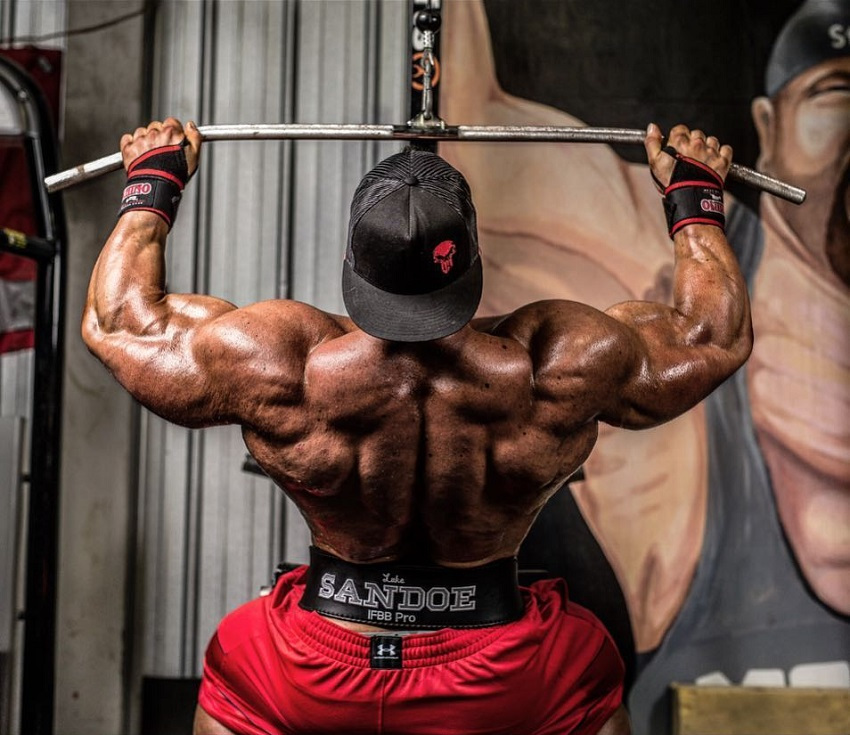 Luke Sandoe doing lat pulldowns while shirtless, looking huge and ripped