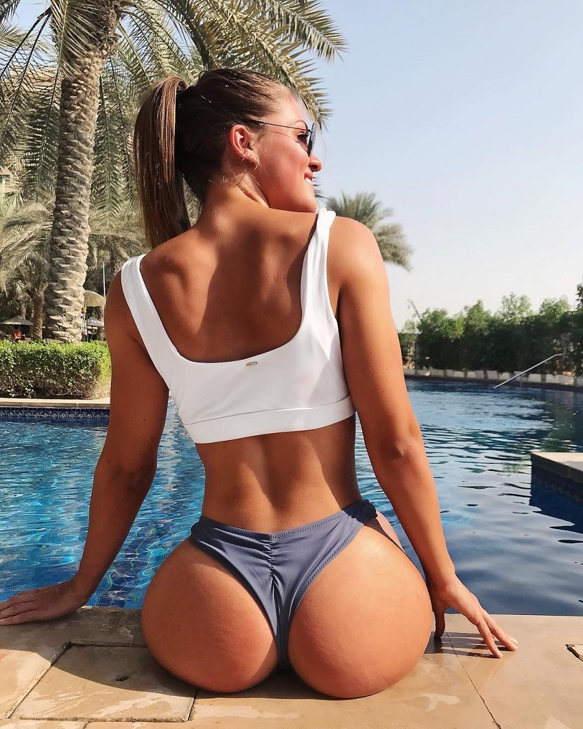 Maria Gad sitting by a pool showing off her curvy glute muscles