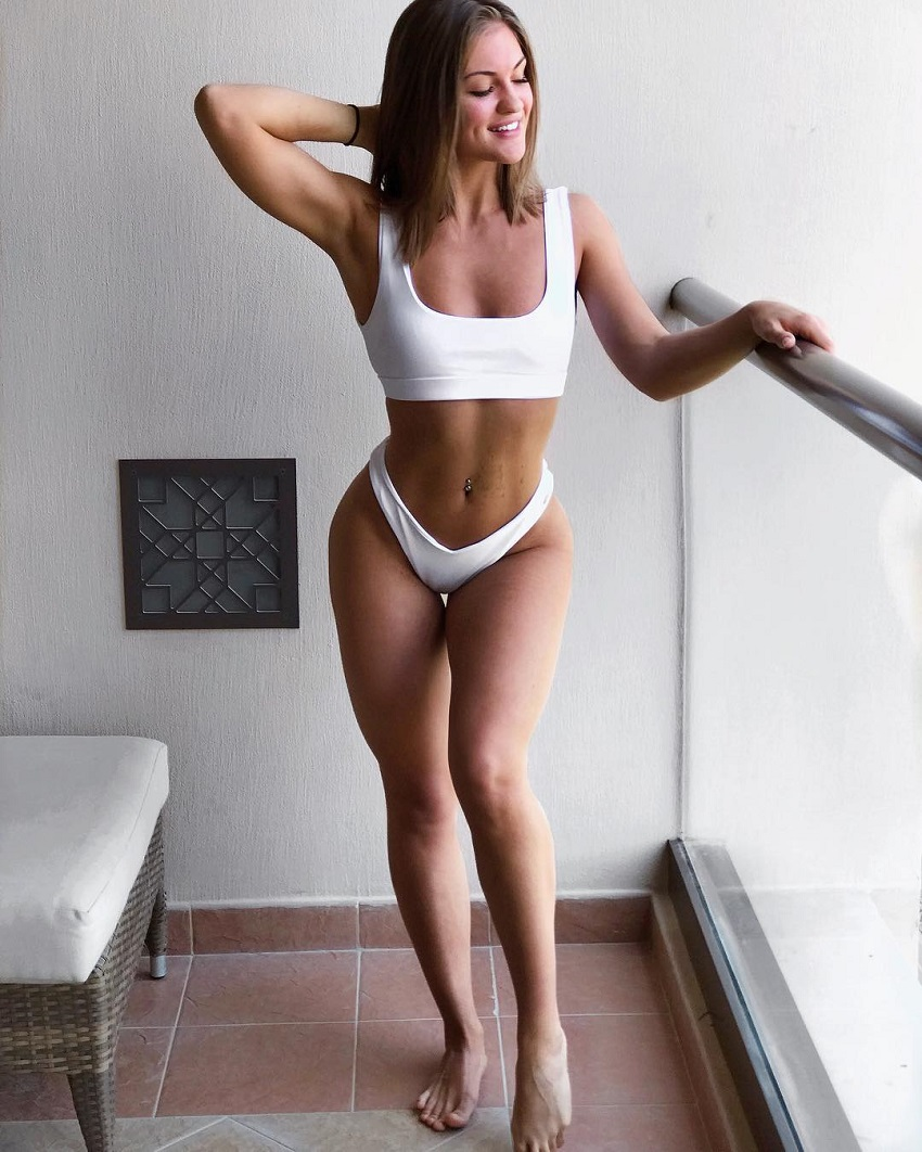 Maria Gad posing near a balcony, looking fit and lean