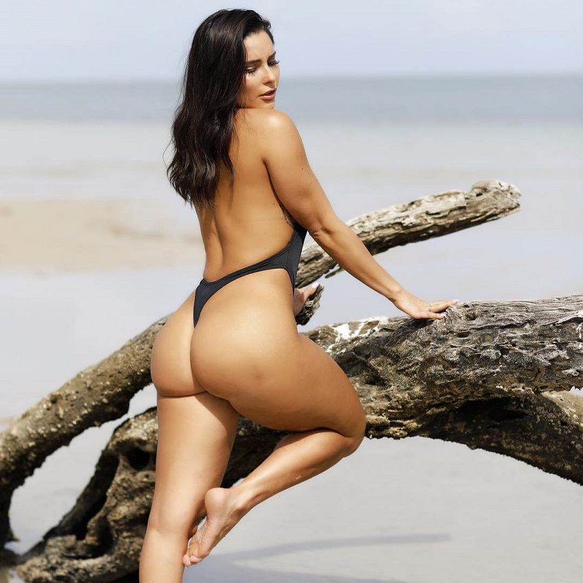 Olivia Delgado posing by a tree on a beach looking curvy