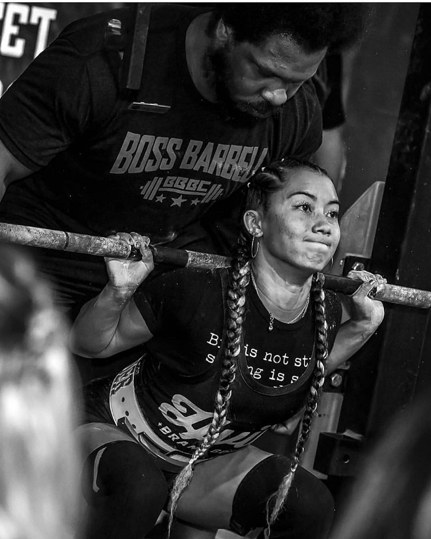 Stacia-Al Mahoe lifting heavy weights during a powerlifting meet