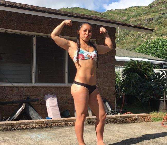 Stacia-Al Mahoe doing a front double biceps flex in a bikini
