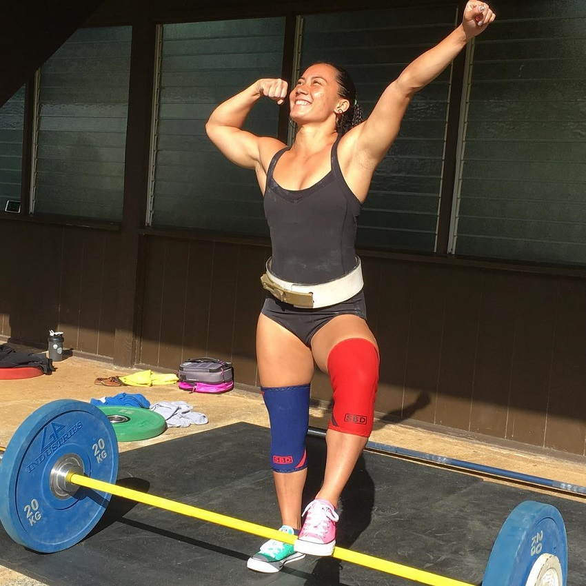Stacia-Al Mahoe standing on a barbell with one leg and flexing her biceps