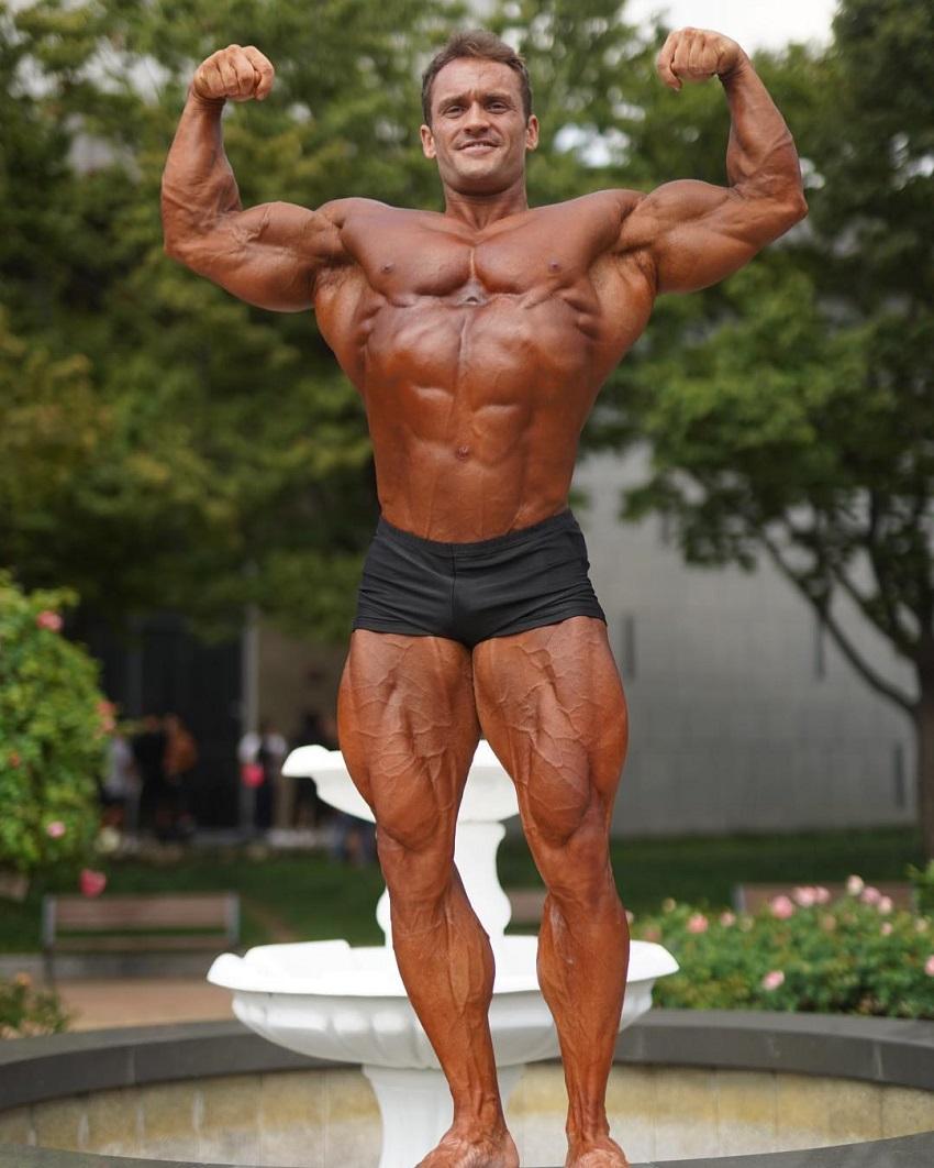 Stanimal De Longeaux doing a shirtless front double biceps flex