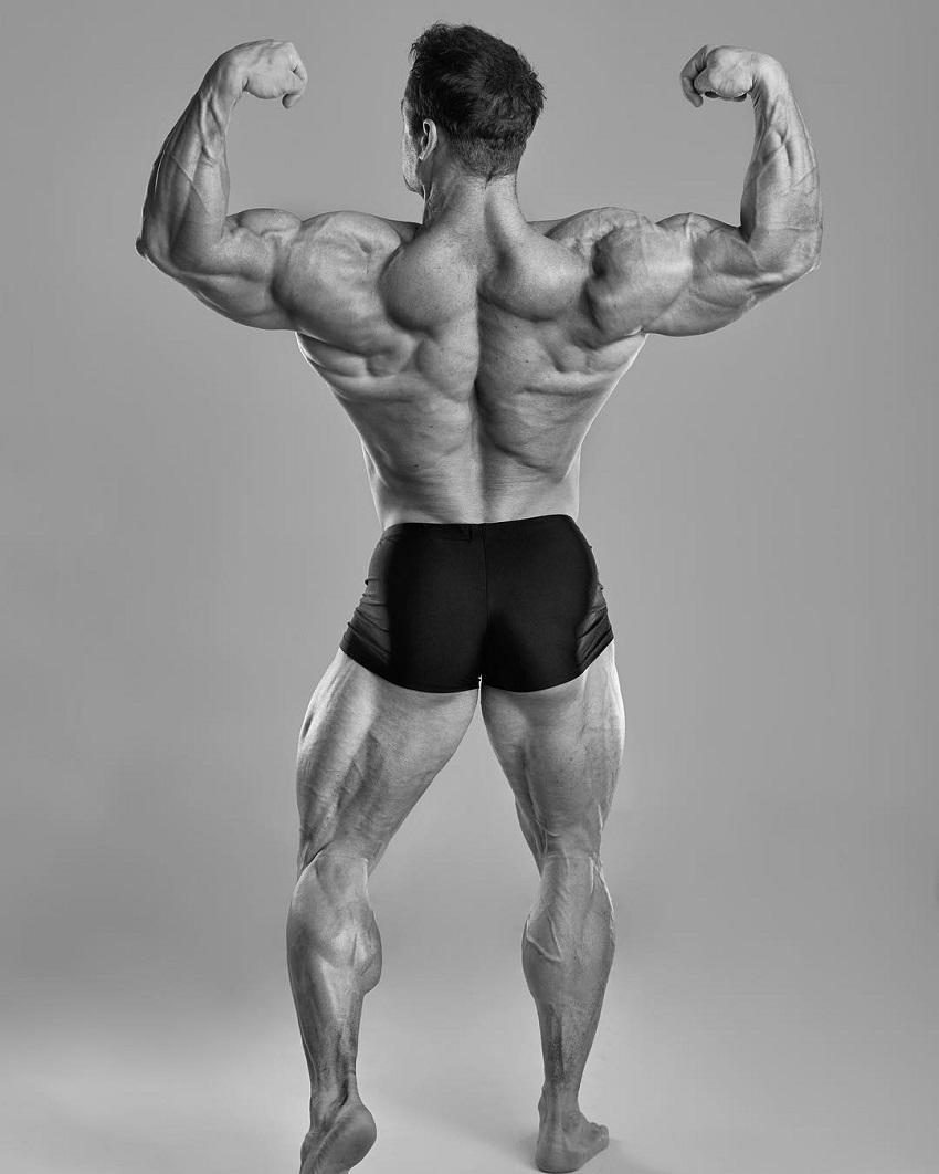 Stanimal De Longeaux performing a back double biceps flex for a photo