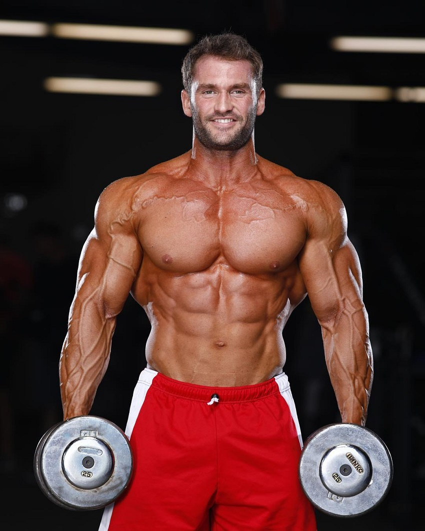 Stanimal De Longeaux standing shirtless with a dumbbell in each hand