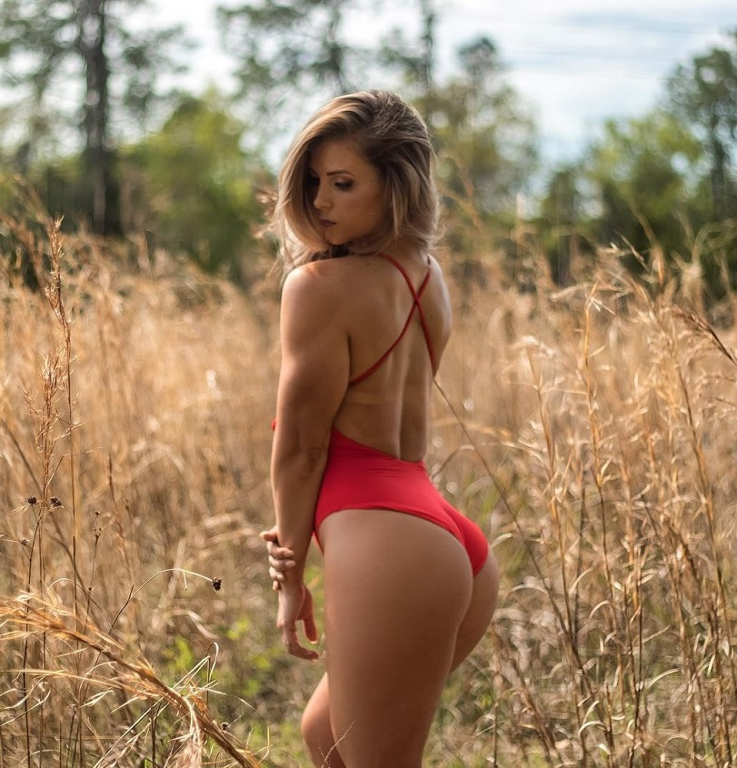Taylor Brown posing in the field of grass looking toned