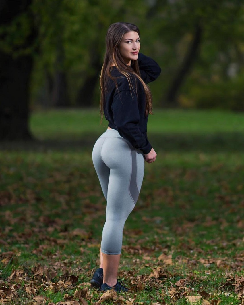 Taylor Spadaccino standing in the woods in her light grey leggings, looking curvy and fit