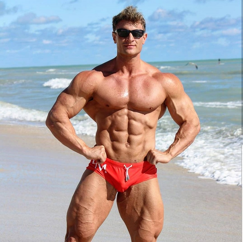 Tyler Garceau flexing shirtless on the beach looking incredible