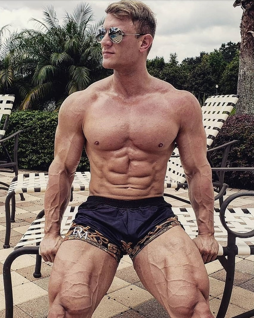 Tyler Garceau posing by a pool looking vascular and ripped