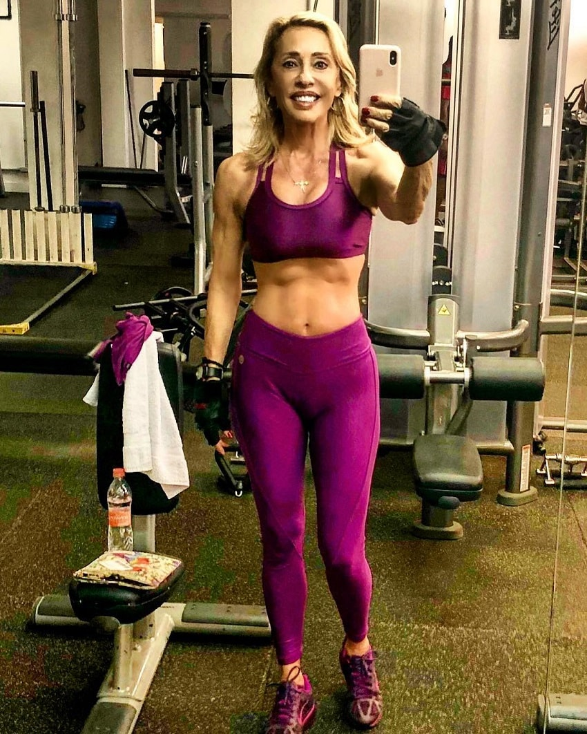 Adriana Miranda taking a photo of her lean midsection in the gym mirror
