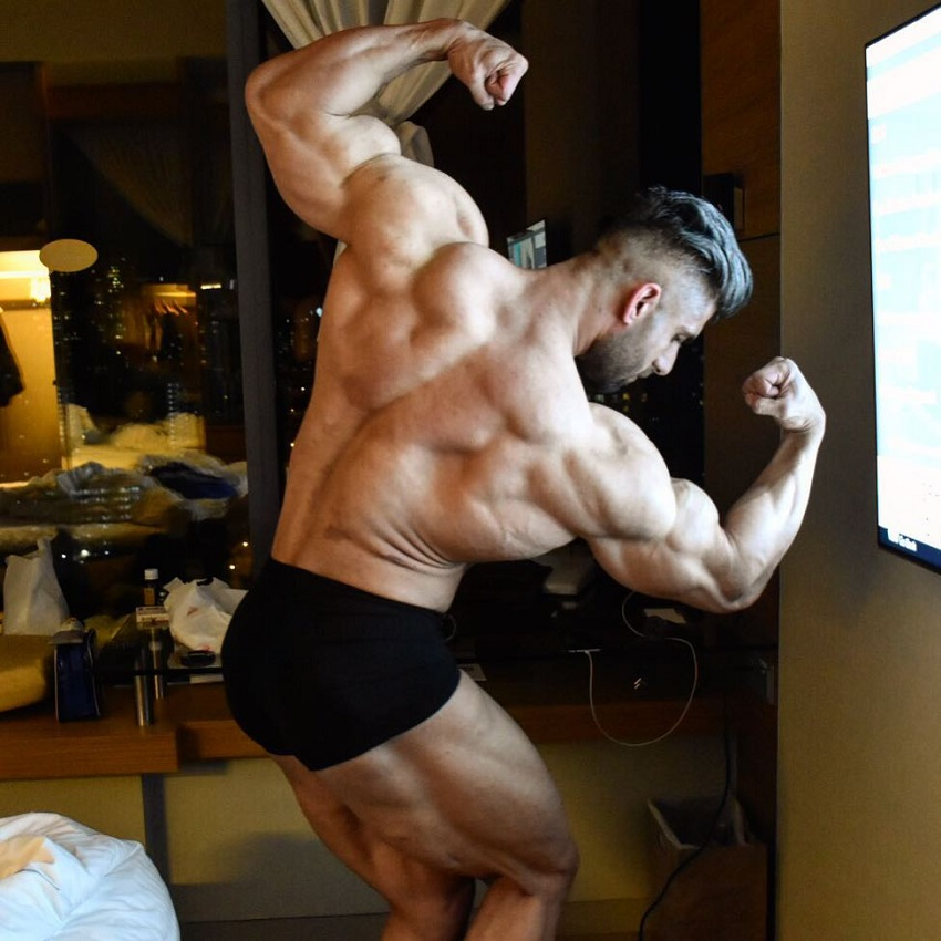 Ahmad Parvin flexing his back and biceps looking fit