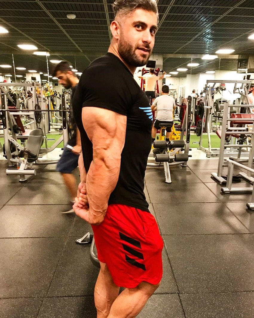Ahmad Parvin flexing his huge and ripped triceps in a gym