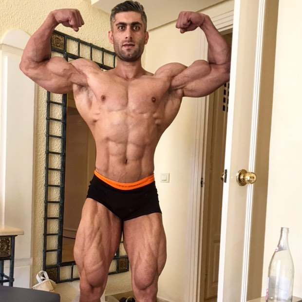 Ahmad Parvin flexing front double biceps in his house