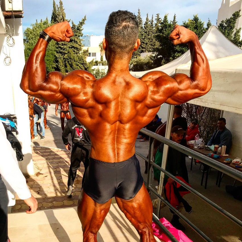 Ahmad Parvin doing a back double biceps outdoors in the contest warm-up area