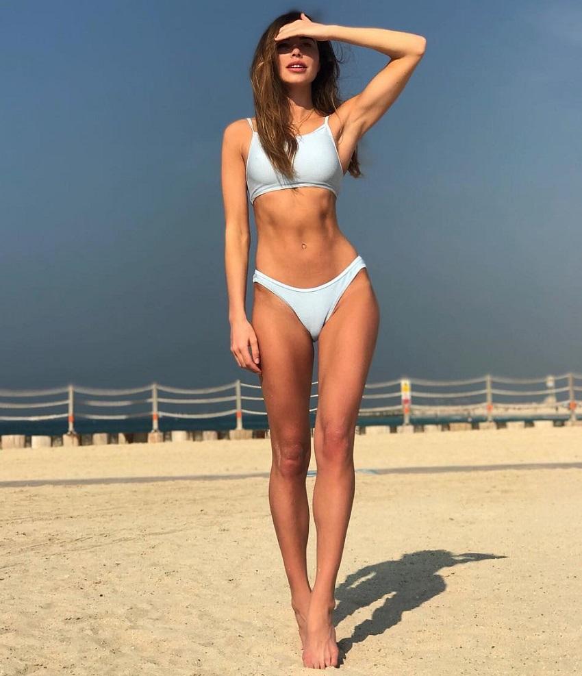 Alex Finch-Collison posing in a bikini on a beach