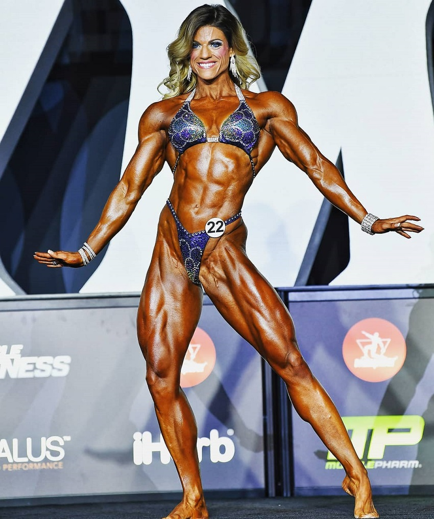 Autumn Swansen posing on the olympia stage looking aesthetic and ripped