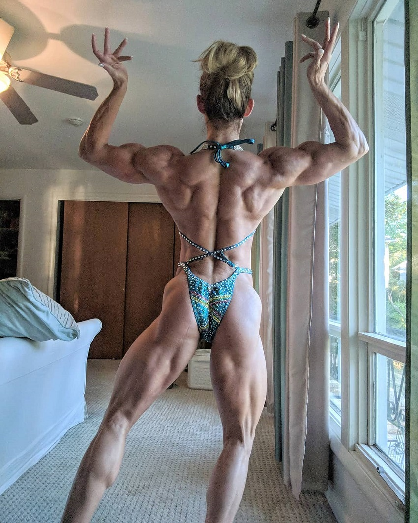 Autumn Swansen performing a muscular back pose in a bikini in a hotel room, looking aesthetic and ripped