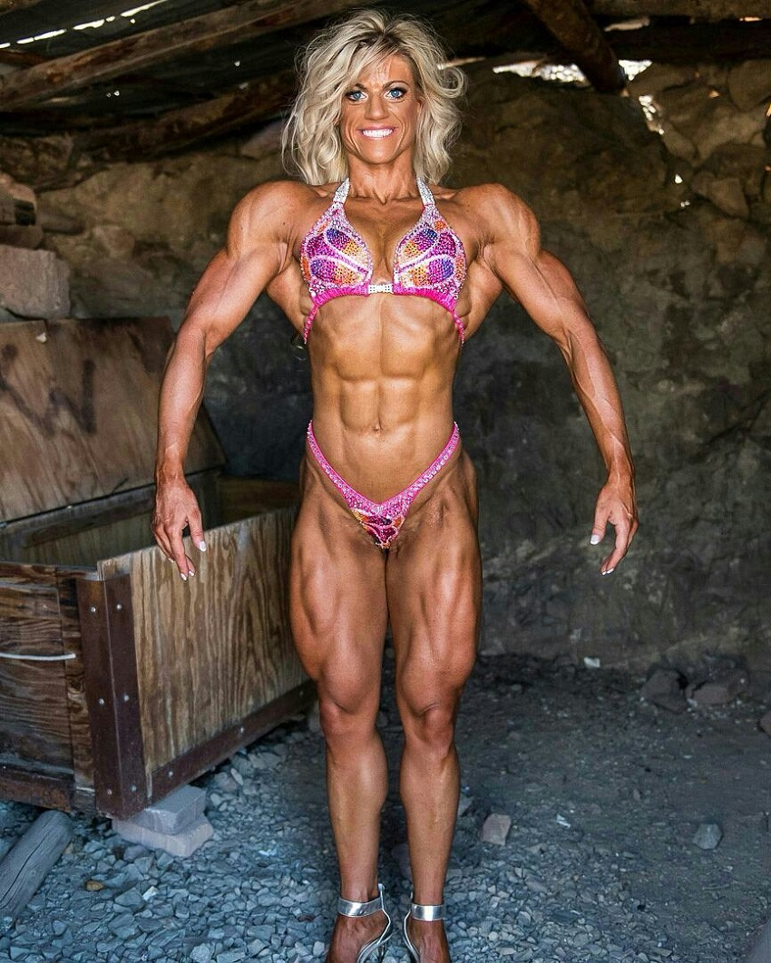Autumn Swansen flexing in a bikini for a camera, looking extremely conditioned and ripped