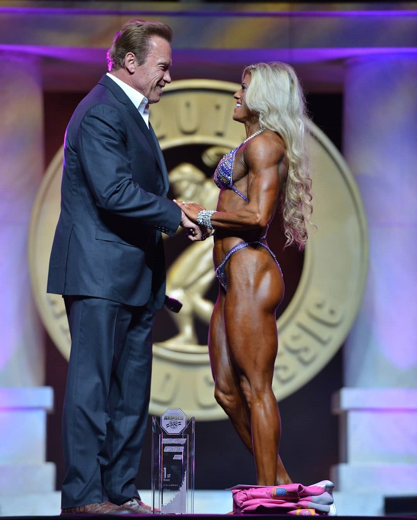 Autumn Swansen shaking hands with Arnold Schwarzenegger at the Arnold Classic fitness contest, looking happy and proud of her victory