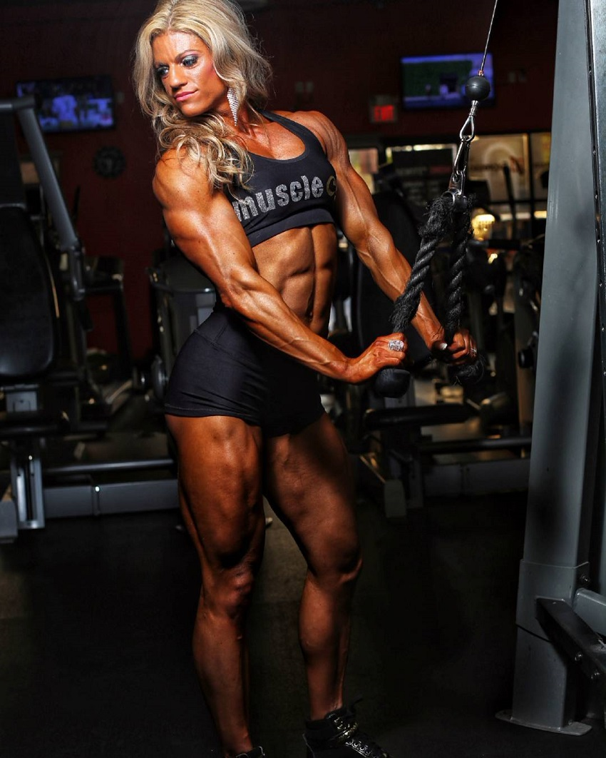 Autumn Swansen training triceps on a cable machine in a gym during a photo shoot