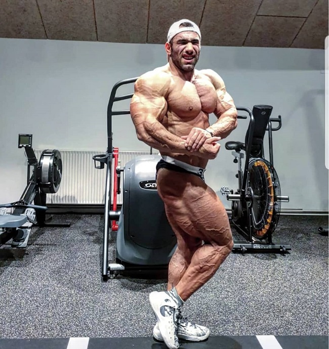 Ayat Bagheri doing a side chest pose for the photo looking ripped and big