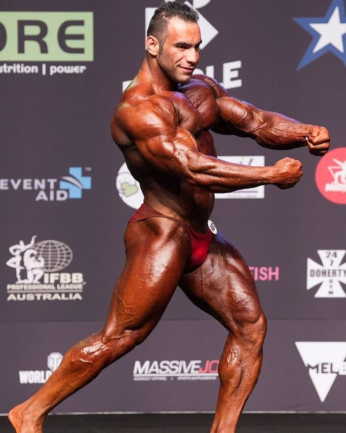 Ayat Bagheri showing his flexed arms from the side on the bodybuilding stages