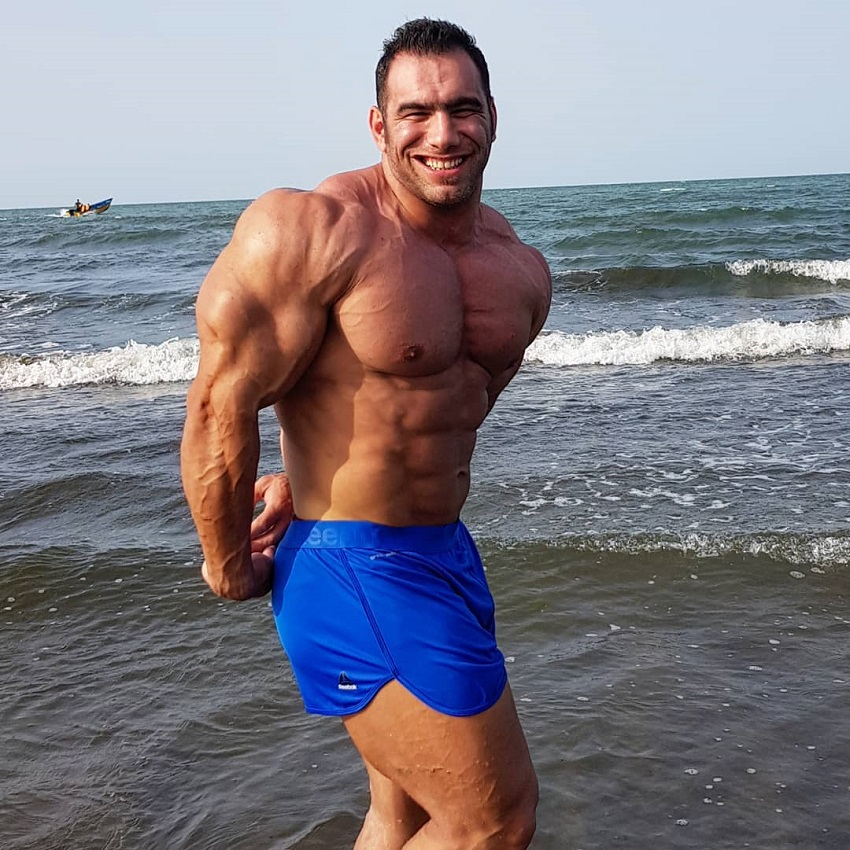 Ayat Bagheri doing a side triceps pose on the beach