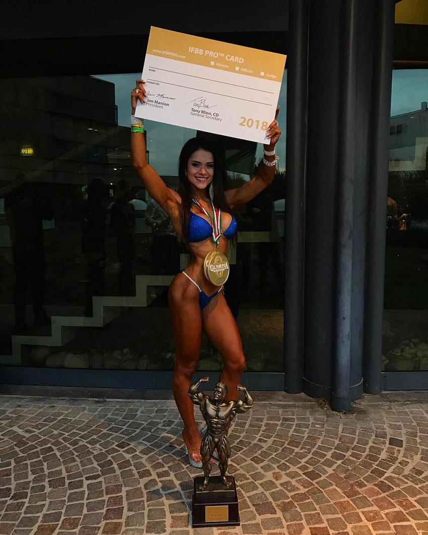 Beatriz Biscaia posing with her IFBB Pro Fitness Card