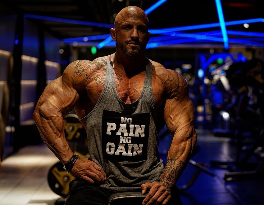 Benjamin Radic posing in a tank top in a gym, looking muscular and ripped
