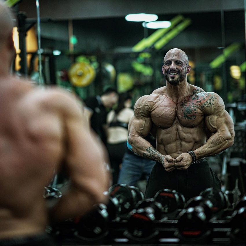Benjamin Radic looking at his striated muscles in a gym mirror