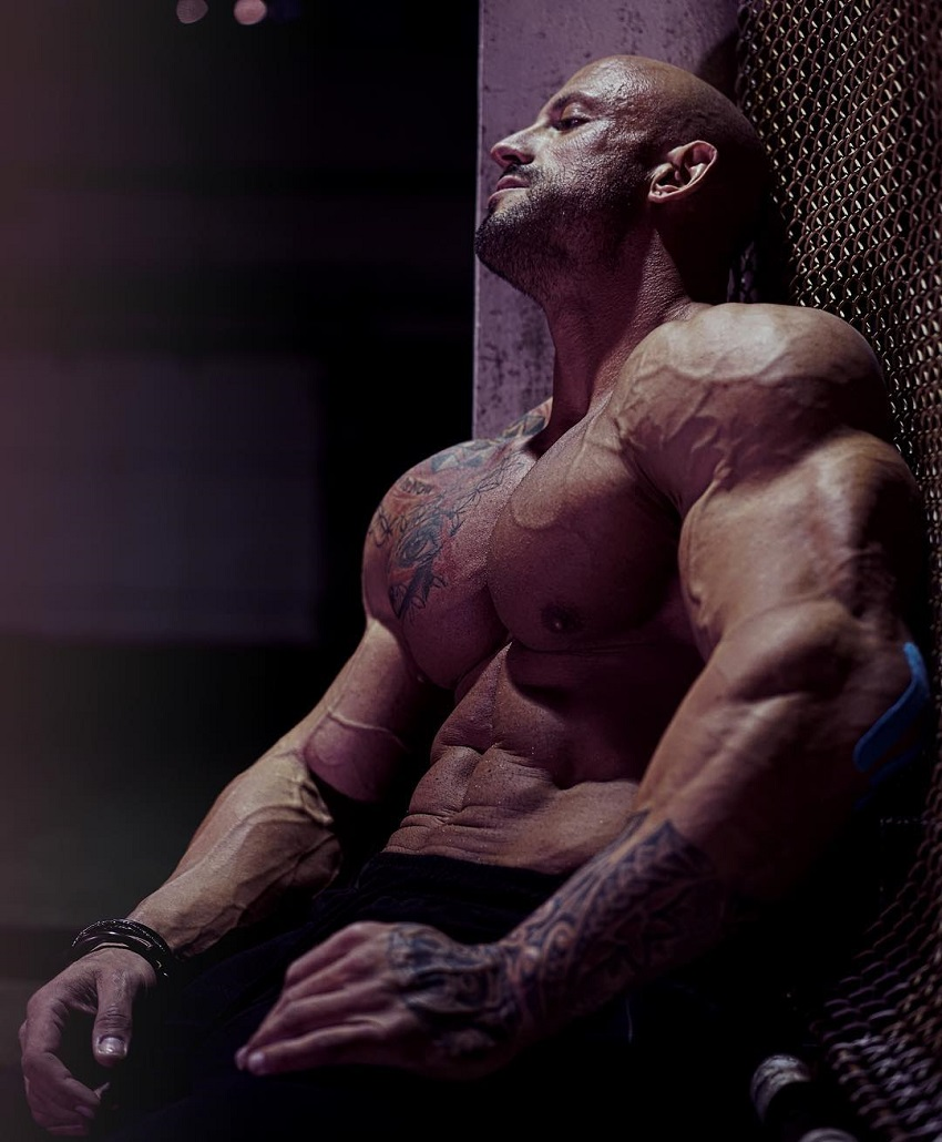 Benjamin Radic resting shirtless seated down, looking exhausted from exercise