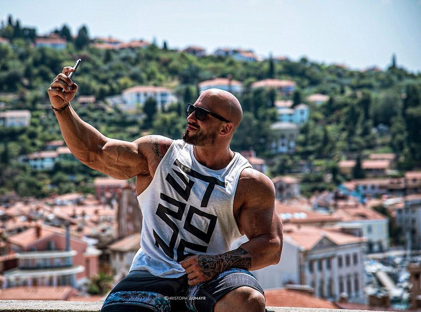 Benjamin Radic wearing a white tank top, taking a selfie of his muscular arms in an exotic location