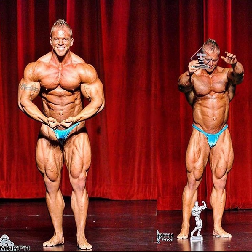 Brandon Beckrich posing with a trophy on a bodybuilding stage