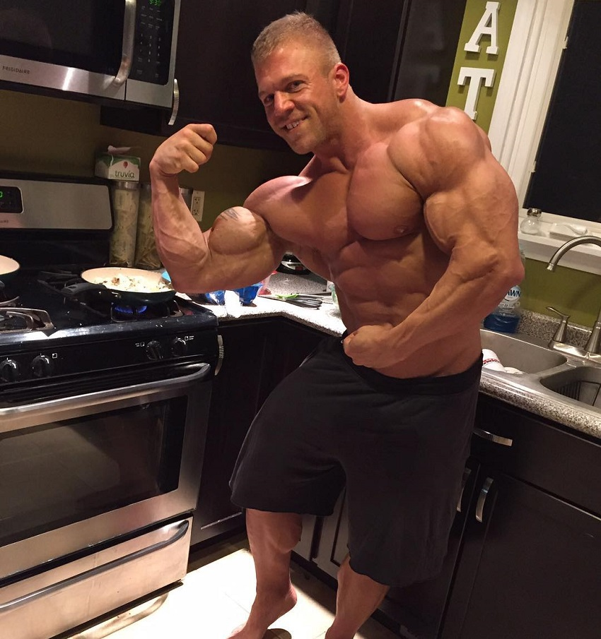 Brandon Beckrich flexing his biceps while being shirtless in the kitchen