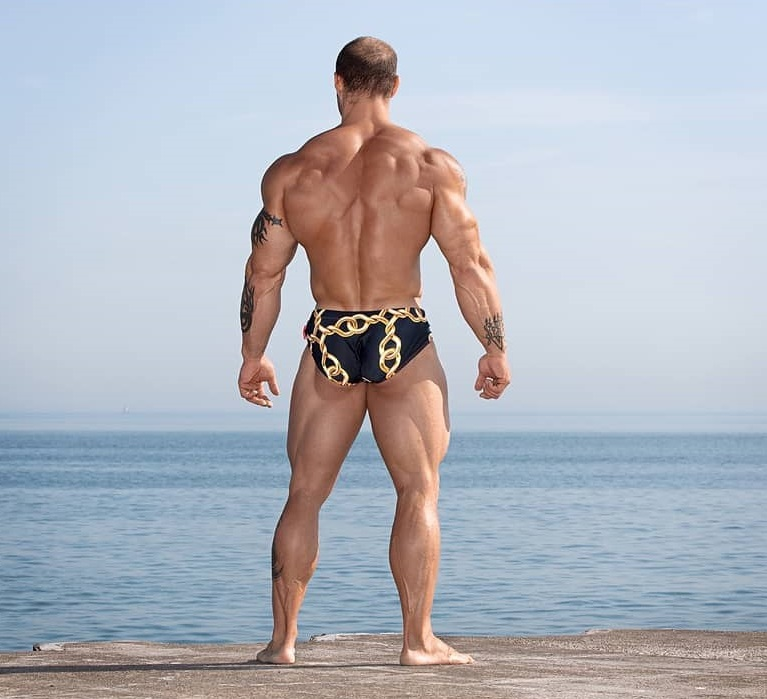 Caleb Blanchard standing by a sea with his back turned toward the camera, looking ripped and huge
