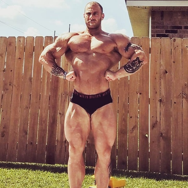 Caleb Blanchard doing a shirtless front lat spread in his backyard