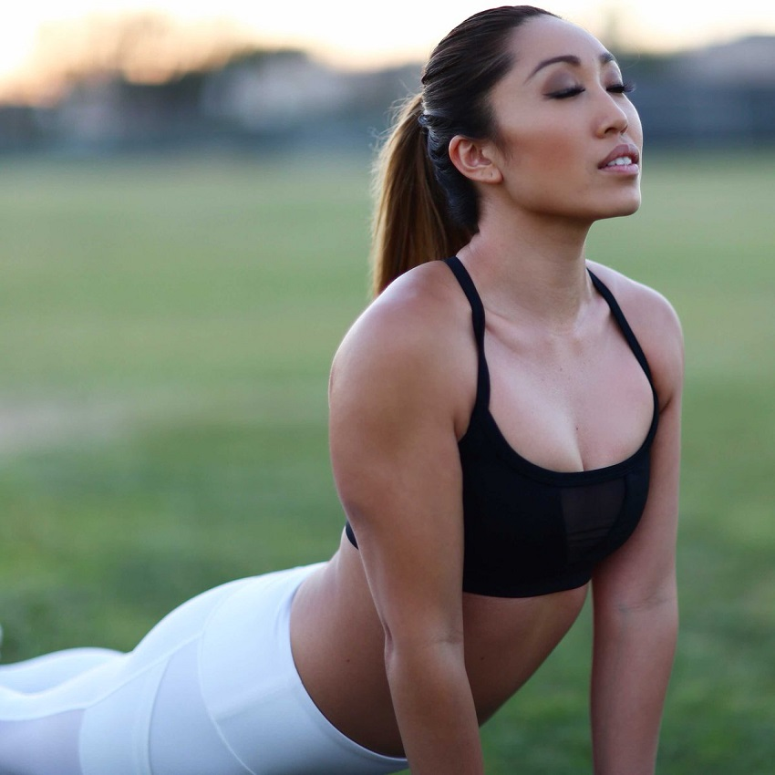 Cassey Ho stretching outdoors looking fit