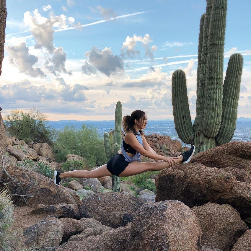 Cassey Ho stretching outdoors in nature