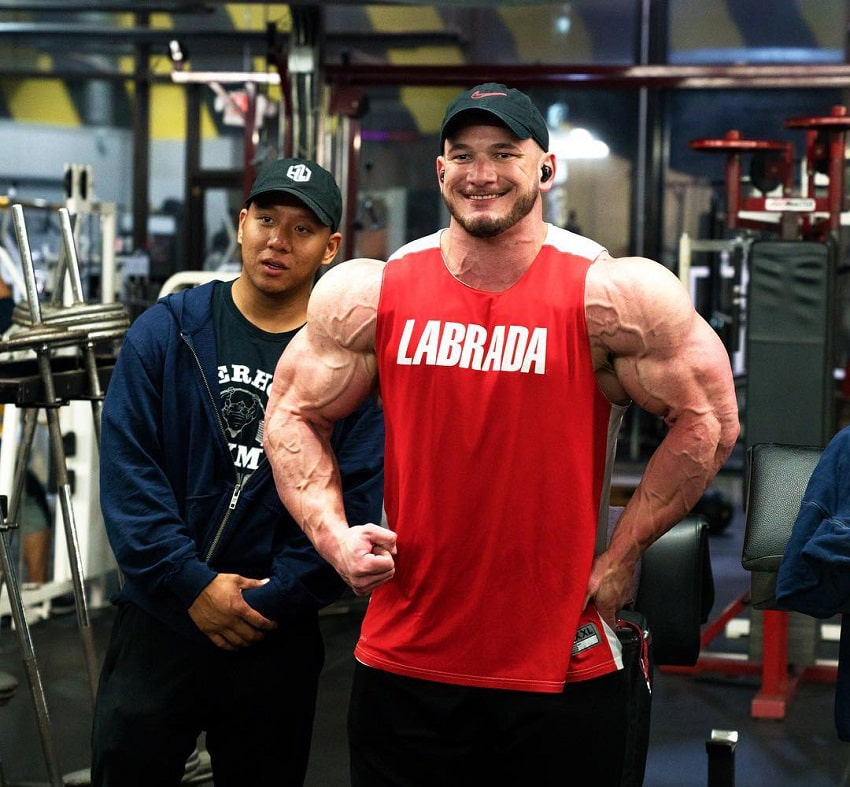 Hunter Labrada flexing for the photo in a red tank top looking massive
