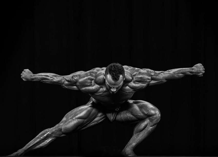Hunter Labrada posing on a bodybuilding stage looking gigantic and ripped