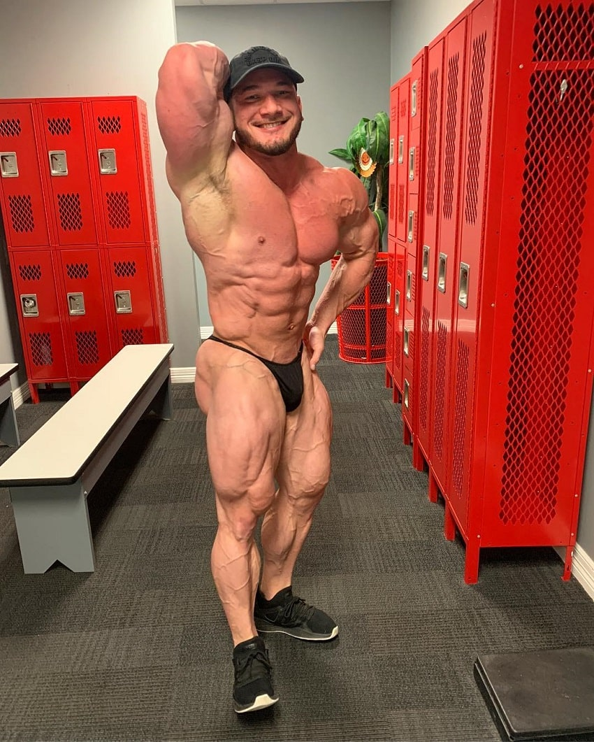 Hunter Labrada flexing his muscles in a locker room looking ripped
