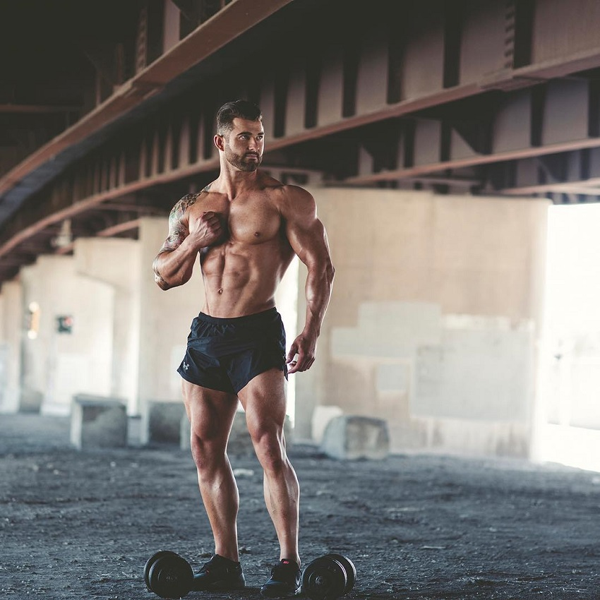 Jase Stevens posing with dumbbells by a bridge, looking ripped