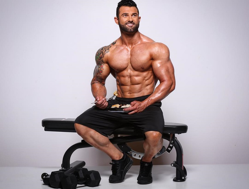 Jase Stevens sitting shirtless on a bench with food in a tupperware